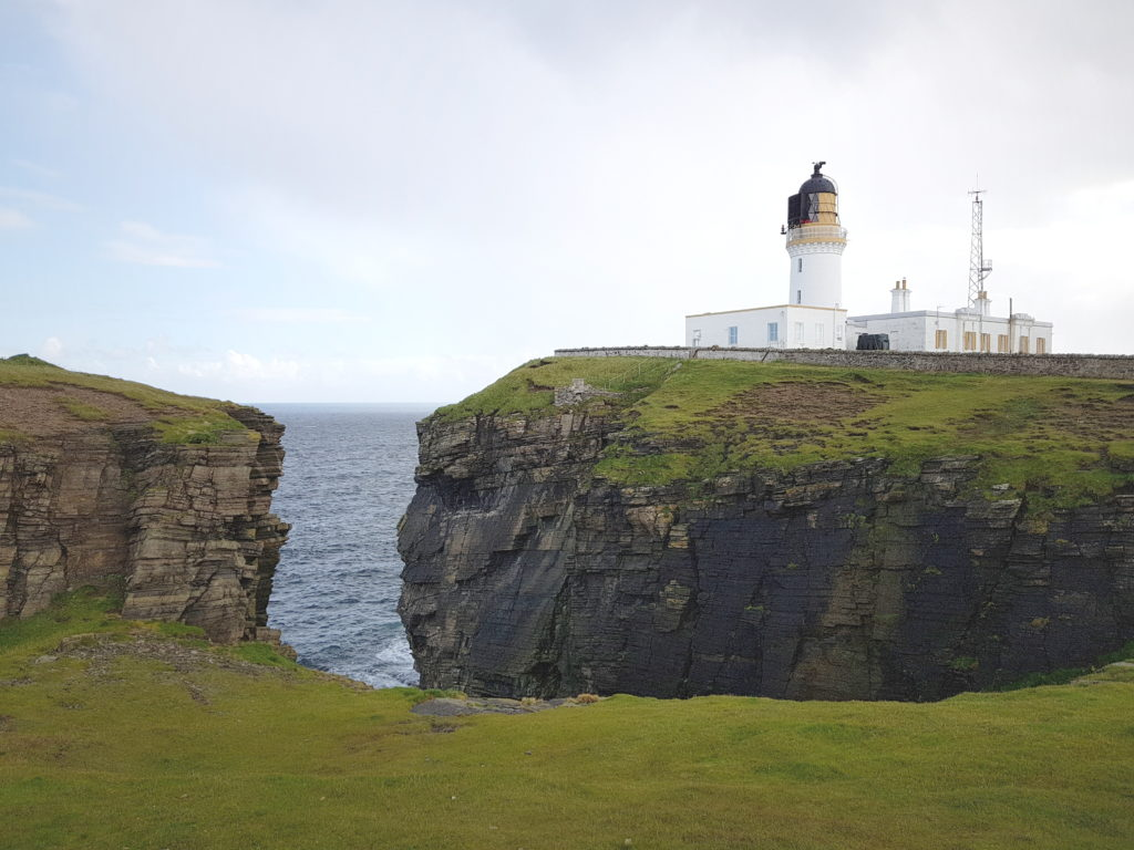 Noss Head Lighthouse is perched high the cliffs and surrounded by sea-stacks